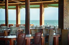 Tabelle in un caffè sotto un baldacchino sulla spiaggia Vista dal caffè sull'oceano Pacifico fotografie stock libere da diritti