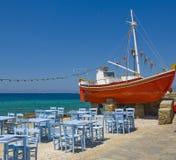 Tabelle in una locanda vicino al mare ed alla barca rossa Immagine Stock Libera da Diritti