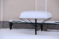 Tabelle und Bank bedeckt mit Schnee Lizenzfreie Stockfotografie