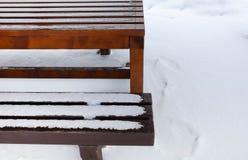 Tabelle und Bank bedeckt mit Schnee Stockbilder