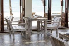 Tabelle und Holzstühle im leeren Café nahe bei dem Meerwasser auf dem Strand, Thailand Lizenzfreie Stockfotografie