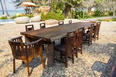 Tabelle und Holzstühle im tropischen Strand nahe bei dem Meerwasser, Thailand Abschluss oben Stockbilder