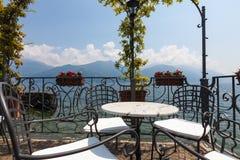 Tabelle und Stühle auf einem Unterlassungssee und Bergen der Terrasse herein Lizenzfreie Stockfotografie