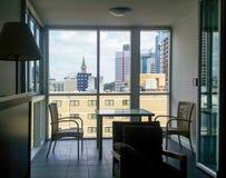 Tabelle und Stühle in der Wohnung durch Fenster ummauern heraus schauen auf Skylinen von Brisbane Queensland Australien am 21. No Stockbilder