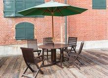 Tabelle und Stühle, die auf einem Bretterboden am Weinlesecafé stehen Stockfotos