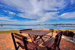 Tabelle und Stühle durch See Lizenzfreie Stockfotos
