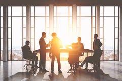 Tabelle und Stühle Gruppe Geschäftsmänner um eine Tabelle Arbeit besprechend gibt heraus Lizenzfreies Stockbild