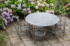 Tabelle und Stühle im Garten mit Farbhortensie Lizenzfreies Stockbild
