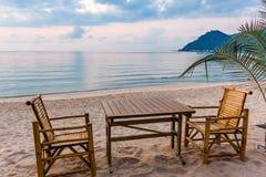 Tabelle und Stühle im Sonnenaufgang an einem tanquil setzen in Thailand auf den Strand Stockbilder