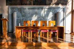Tabelle und Stühle in sonnenbeschienem Raum Aula Baratto Stockbild