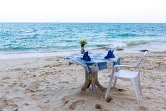 Tabelle und Stuhl und eine blaue Tischdecke auf dem Strand lizenzfreie stockfotos