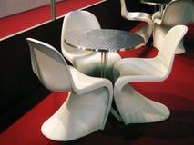 Tabelle und weiße Stühle Stockbild