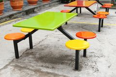 Tabelle variopinte e sedili per il cibo all'aperto Fotografia Stock Libera da Diritti