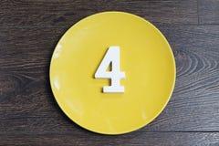 Tabelle vier auf einer gelben Platte Stockfoto