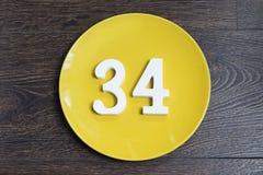 Tabelle vierunddreißig auf der gelben Platte Lizenzfreies Stockfoto