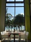 Tabelle vor einem Fenster mit Strandansicht Stockfotos