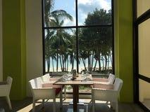 Tabelle vor einem Fenster mit Strandansicht Lizenzfreies Stockbild