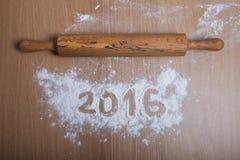 Tabellen 2016 auf dem Mehl, das auf hölzernem Hintergrund verschüttet wird Selektives f Lizenzfreies Stockbild