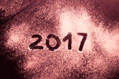 Tabellen 2017 auf dem Mehl, das auf schwarzem Metallhintergrund verschüttet wird getont Lizenzfreie Stockbilder