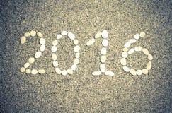 Tabellen 2016 auf einem natürlichen Hintergrund des großen Sandes oder des kleinen pebb Lizenzfreie Stockfotos