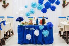Tabellen av bruden och brudgummen med den blåa dekoren och inskriften i ryss där är lycka arkivbild