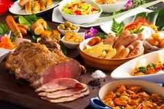Tabellen av mat med grillat nötkött, korvar, pasta, stekte tomater Arkivfoton