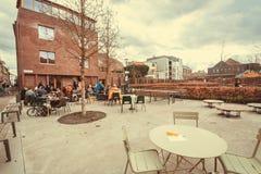 Tabellen des modernen Restaurants im Freien nahe Stadtpark und einige Leute, die zu Mittag essen Stockbilder