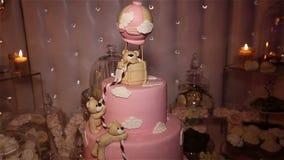 Tabellen med sötsaker, rosa färger bakar ihop 1 år, godisstången, läckra sötsaker på godisbuffé, kakan med en björngröngöling, mö arkivfilmer