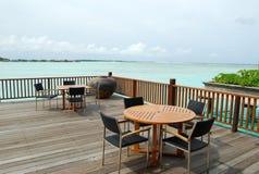Tabellen und Lehnsessel unter Sonnenschirmen lizenzfreies stockbild