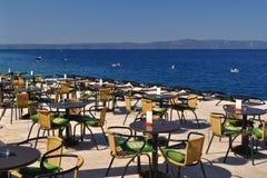 Tabellen und Stühle des Restaurants im Strand von Podgora Stockfotografie