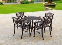 Tabellen und Stühle neben einem Garten Lizenzfreies Stockfoto