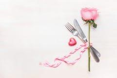 Tabellengedeck: rosafarbene Blume, Tischbesteck und Band auf hellem Hintergrund, Draufsicht Stockbild
