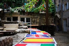 Tabeller i gatakafét som målas i färger av flaggor av olika länder Spanien, Förenade kungariket, Frankrike terrass Arkivbilder