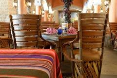 Tabeller med bordsservis i tom restaurang Fotografering för Bildbyråer