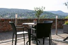 Tabeller med stolar på terrass av den kust- restaurangen Arkivfoto