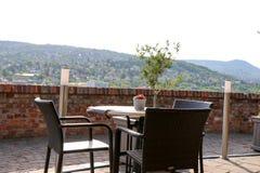 Tabeller med stolar på terrass av den kust- restaurangen Arkivbilder