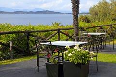 Tabeller och järnstolar på terrass med havet beskådar (Grekland) Arkivfoton