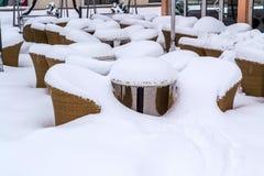 Tabeller och stolar framme av restaurangen som begravas i snö Arkivbild