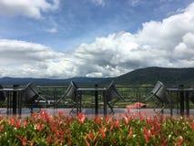 Tabeller och stolar med berg- och molnbakgrund Arkivfoto