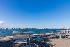 Tabeller och stolar på solig dag på fanen Pier Park Boston, Massachusetts Nästan hav arkivbild