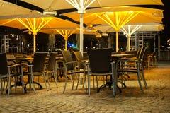 Tabeller och stolar utanför en restaurang på natten royaltyfri bild