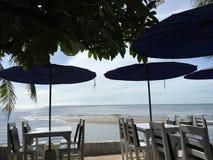 Tabeller och strandparaplyer vid havet på sundawn på Huahin, Thailand royaltyfri fotografi