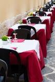 Tabeller ställer in och tömmer stolar uppställda i en restaurang i Ortigia, arkivfoton