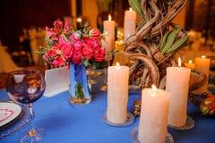 Tabellgarnering som består av blommor och stearinljus Fotografering för Bildbyråer