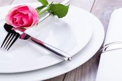 Tabellinställning med en enkel rosa färgros Fotografering för Bildbyråer