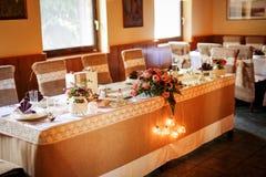 Tabellinställning på ett lyxigt bröllop, härligt orange ljus royaltyfria foton