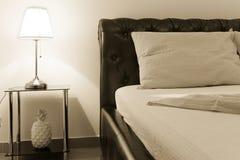 Tabelllampa och säng arkivbild