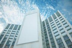 Tabellone per le affissioni bianco in bianco fra i centri di affari al backg del cielo blu Immagini Stock