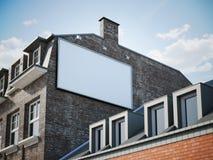 Tabellone per le affissioni in bianco che appende nell'ombra della costruzione classica Immagini Stock