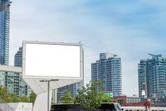 Tabellone per le affissioni in bianco davanti alle costruzioni alte di appartamento e dell'ufficio immagini stock